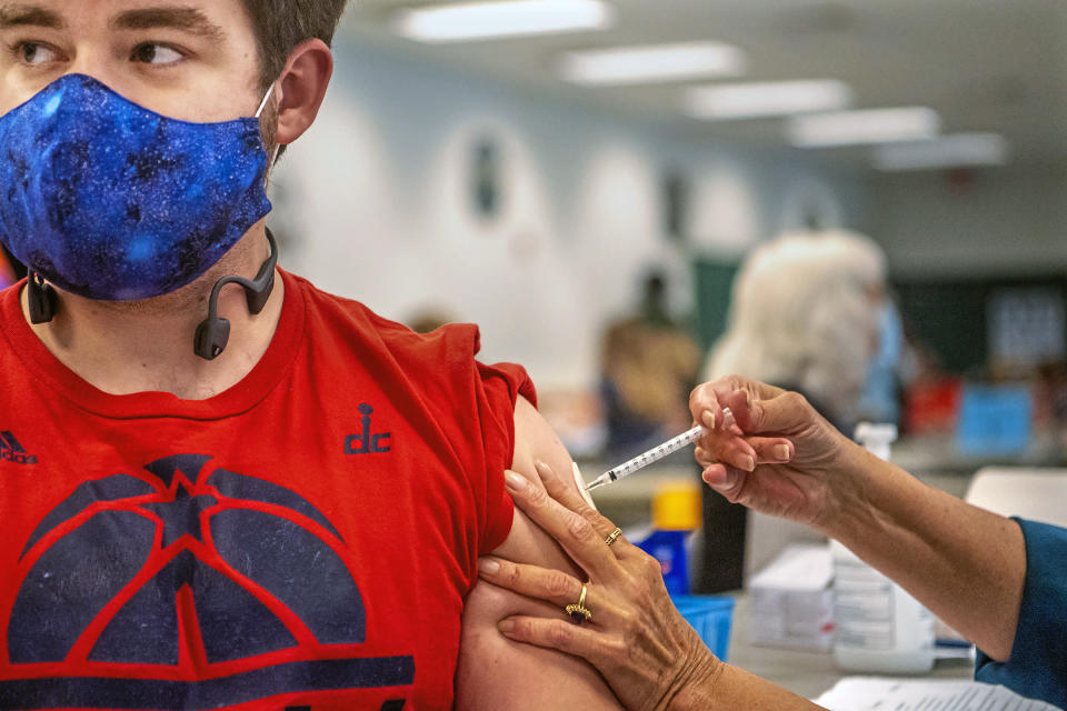 Eric Pierce, 24, of Pittsburgh, receives a COVID-19 vaccine at a clinic run by Spartan Pharmacy at the Broughton Volunteer Fire Department, Wednesday, April 7, 2021, in South Park, Pa. (Alexandra Wimley/Pittsburgh Post-Gazette via AP)