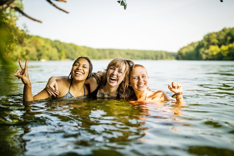 Portrait of three young women together in lake. Group of young female friends enjoying swimming together in lake.