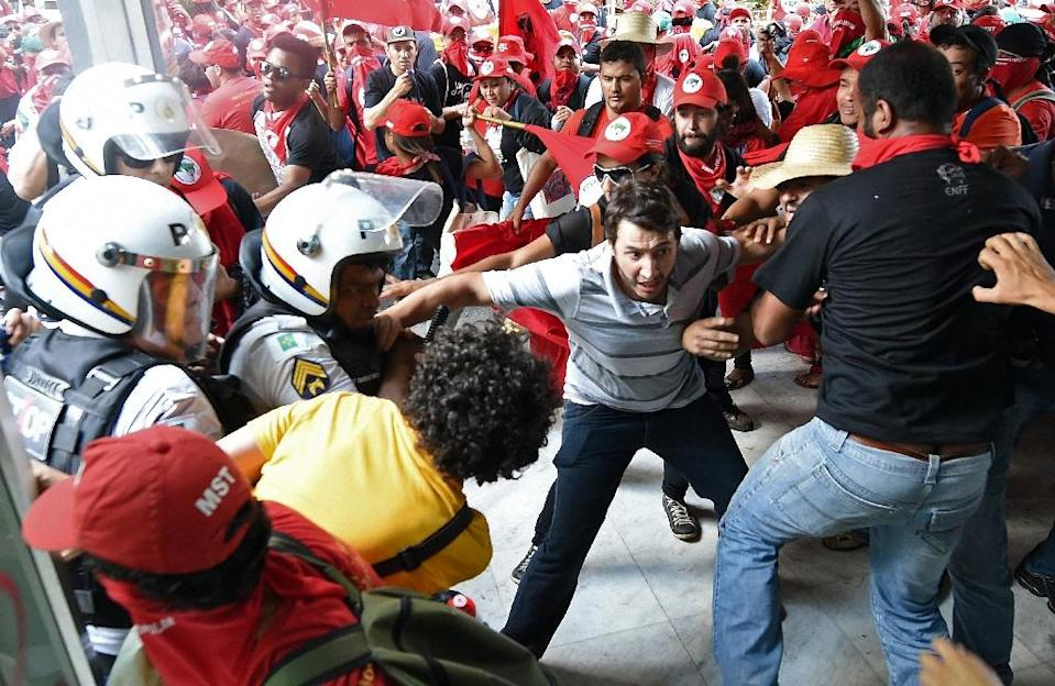 Members of the Landless Movement clash with the police during a demonstration against a fiscal adjustment and budget cuts proposed by the government, outside the Agriculture Ministry in Brasilia, on September 23, 2015 (AFP Photo/Evaristo SA)