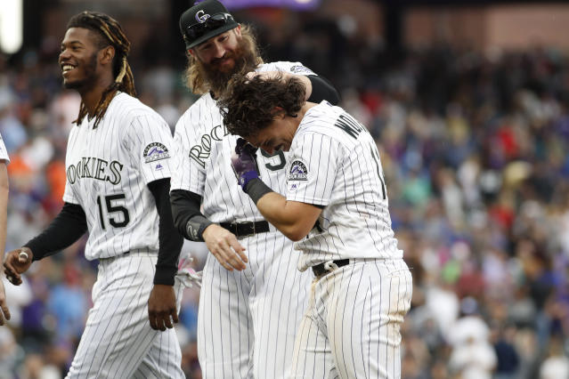 Colorado Rockies' Tony Wolters, front, is congratulated by Charlie Blackmon, center, as Raimel Tapia joins in after Wolters hit a sacrifice fly to bring in the winning run off Baltimore Orioles relief pitcher Mychal Givens in the ninth inning of a baseball game Sunday, May 26, 2019, in Denver. (AP Photo/David Zalubowski)