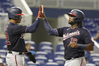 Washington Nationals' Juan Soto (22) and Josh Bell (19) score on a single by Keibert Ruiz during the fifth inning of a baseball game against the Miami Marlins, Monday, Sept. 20, 2021, in Miami. (AP Photo/Marta Lavandier)