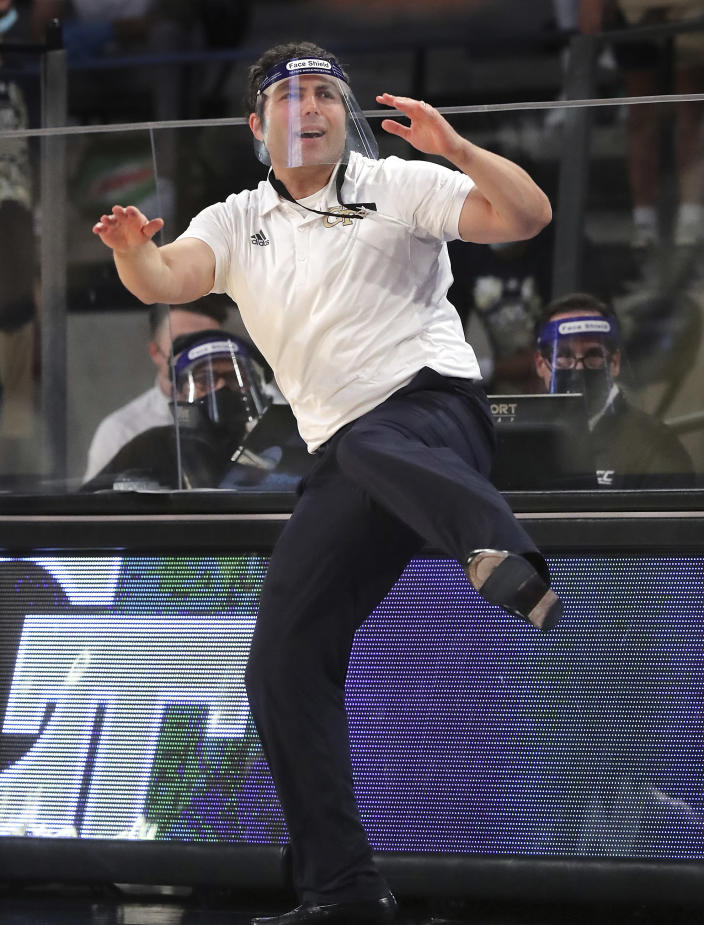 Georgia Tech head coach Josh Pastner uses some body English and a leg kick while coaching his team to a come from behind 72-67 victory over North Carolina during an NCAA college basketball game Wednesday, Dec. 30, 2020, in Atlanta. (Curtis Compton/Atlanta Journal-Constitution via AP, Pool)