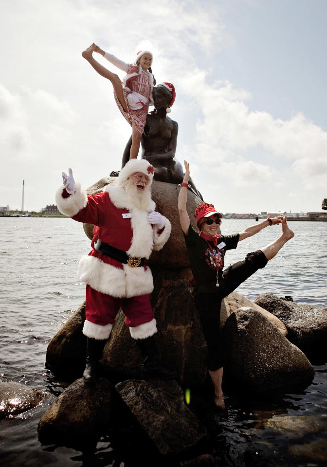 A Santa poses during the World Santa Claus Congress next to the Little Mermaid statue in the harbour of Copenhagen, on Monday, July 18, 2011. The World Santa Claus Congress has taken place in the Dyrehavsbakken amusement park (usually shortened to Bakken) north of Copenhagen since 1957. (AP Photo/POLFOTO, Joachim Adrian) DENMARK OUT