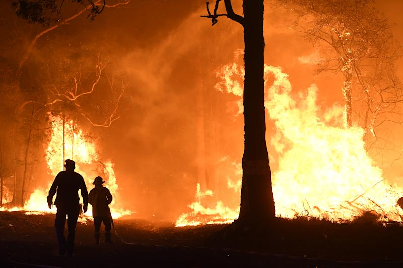 RFS, NSW Fire and Rescue, NPWS officers and local residents fight a bushfire encroaching on properties near Termeil on the Princes Highway between Bateman's Bay and Ulladulla south of Sydney,Tuesday, December, 3, 2019. (AAP Image/Dean Lewins) NO ARCHIVING