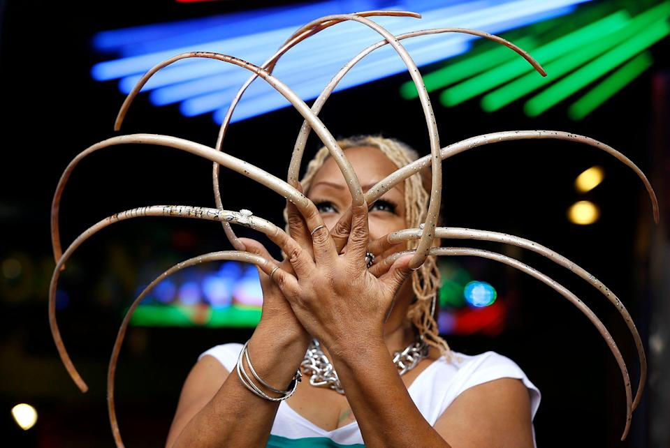"""Ayanna Williams displays her 23-inch nails at a book launch in London. Williams is featured in a book entitled """"Ripley's Believe it or Not! 2015 Annual, Reality Shock."""""""