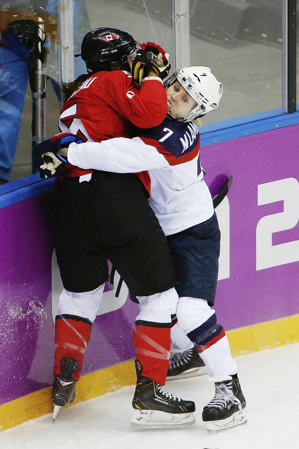 Monique Lamoureux of the United States (7) pins Lauriane Rougeau of Canada (5) against the boards during the first period of the women's gold medal ice hockey game at the 2014 Winter Olympics, Thursday, Feb. 20, 2014, in Sochi, Russia. (AP Photo/Julio Cortez)