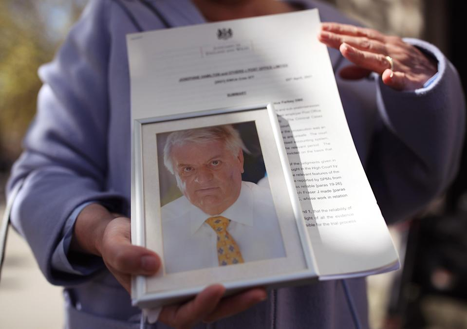 Karen Wilson, widow of postmaster Julian Wilson who died in 2016, holds his picture outside an earlier hearing (PA) (PA Wire)