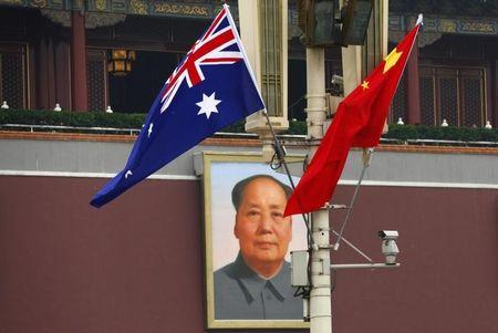 The Australian national flag flies next to the Chinese national flag in front of the giant portrait of former Chairman Mao Zedong in Beijing