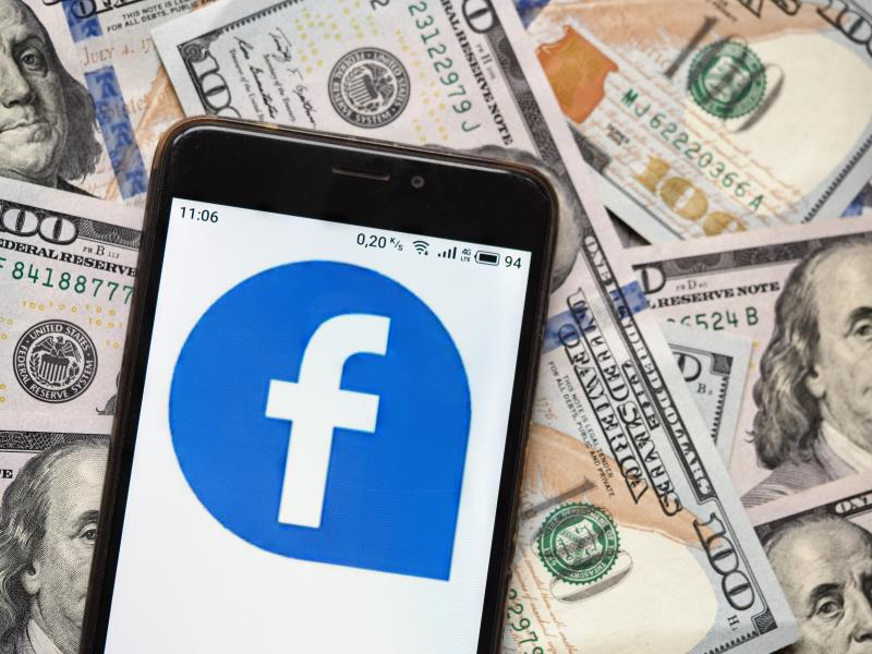UKRAINE - 2020/09/04: In this photo illustration a Facebook logo seen displayed on a smartphone with 100 dollar bills in the background. (Photo Illustration by Igor Golovniov/SOPA Images/LightRocket via Getty Images)