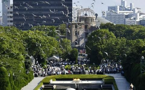 Doves fly over the Peace Memorial Park with the Atomic Bomb Dome in the background, at a ceremony in Hiroshima - Credit: Reuters