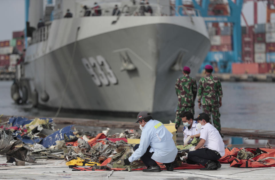 Investigators inspect pieces of the Sriwijaya Air flight SJ-182 retrieved from the Java Sea where the passenger jet crashed on Jan. 9, as an Indonesian Navy ship prepares to dock at Tanjung Priok Port in Jakarta, Indonesia, Thursday, Jan. 21, 2021. Indonesian authorities on Thursday ended the search for the wreckage of the plane that nose-dived into the sea, killing all of its passengers on board. (AP Photo/Dita Alangkara)