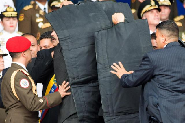 <p>Security members protect Venezuelan President Nicolas Maduro after his speech was interrupted in Caracas, Venezuela, on Aug. 4, 2018. Venezuela's Minister of Communication Jorge Rodriguez confirmed on Saturday night an attempted attack against President Nicolas Maduro. The attack happened during a speech by Maduro commemorating the 81st anniversary of the country's National Guard. (Photo: Xinhua via ZUMA Wire) </p>