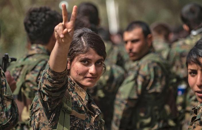 Fighters of the Kurdish-led Syrian Democratic Forces, women prominent among them, celebrate victory after nearly five years of fighting the most brutal jihadist group in modern history (AFP Photo/Delil souleiman)