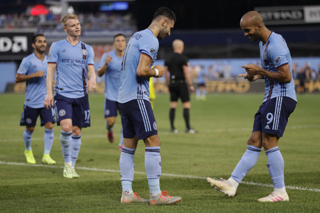 Teammates watch as New York City FC midfielder Valentin Castellanos, center, and New York City FC forward Heber, right, do a little dance after Castellanos scored during the first half of an MLS soccer match against Columbus Crew, Wednesday, Aug. 21, 2019, in New York. (AP Photo/Kathy Willens)