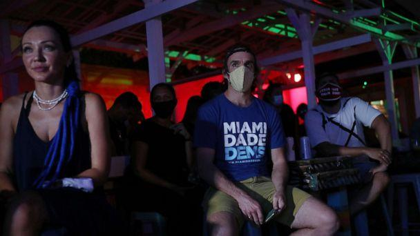 PHOTO: Dan Royles and other people watch at Gramps bar a streaming broadcast of the first debate between President Donald Trump and Democratic presidential nominee Joe Biden, Sept. 29, 2020, in Miami. (Joe Raedle/Getty Images)