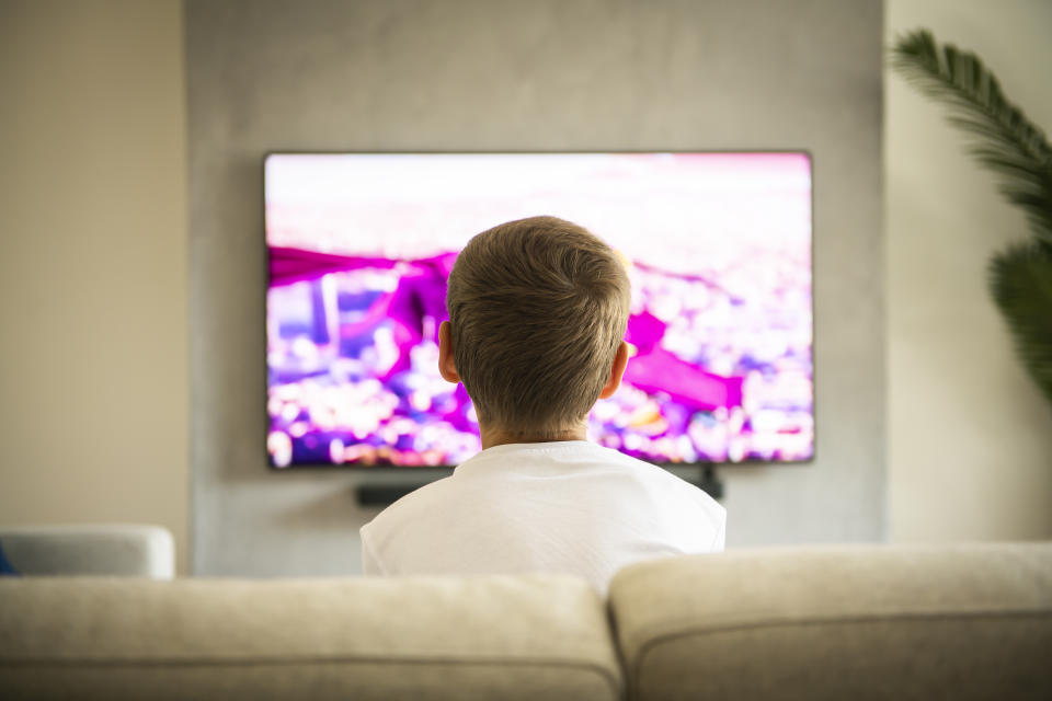 The Back view image of cute boy sitting on sofa and watching TV.