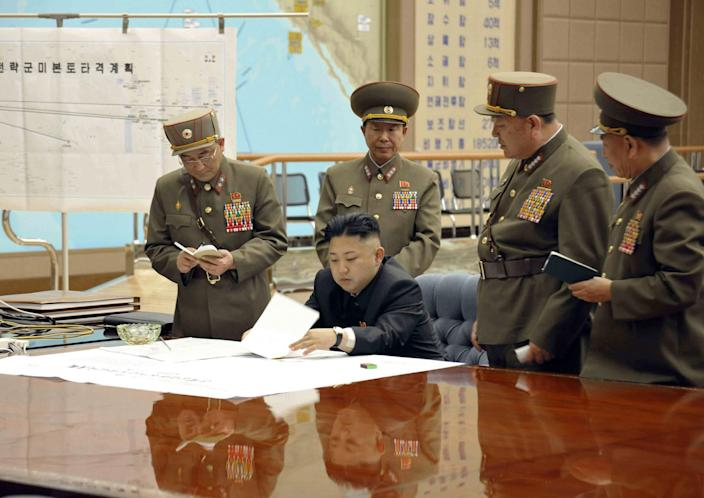 """<p>North Korean leader Kim Jong-un presides over an urgent operation meeting on the Korean People's Army Strategic Rocket Force's performance of duty for firepower strike at the Supreme Command in Pyongyang, March 29, 2013. The sign on the left reads, """"Strategic force's plan to hit the mainland of the U.S."""" (KCNA/Reuters) </p>"""