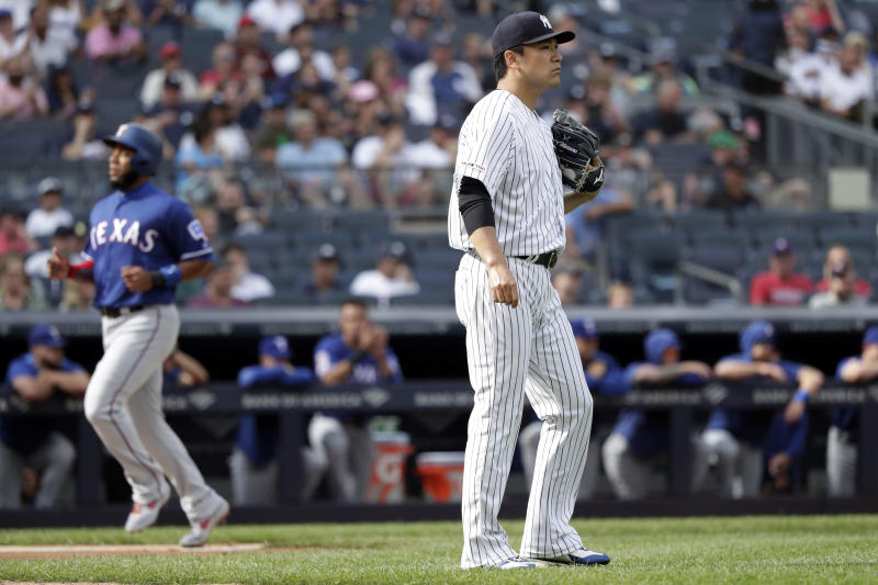 New York Yankees pitcher Masahiro Tanaka, right, looks away as Texas Rangers' Elvis Andrus scores a run during the first inning of a baseball game Monday, Sept. 2, 2019, in New York. (AP Photo/Adam Hunger)
