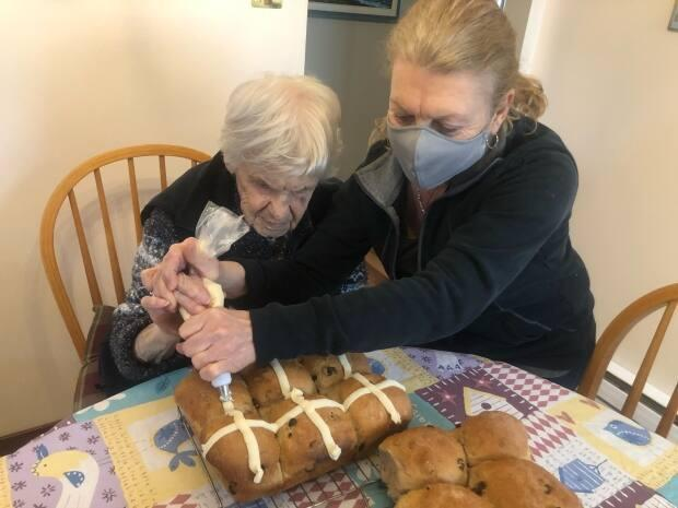 Pierrette McKnight and her mother, Mai Gosselin, add icing to a fresh batch of hot cross buns on Good Friday.