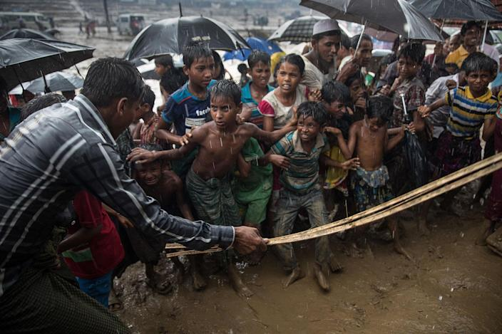 <p>A man hits anxious Rohingya children with a cane as things get out of control during a humanitarian aid distribution while monsoon rains continue to batter the area causing more difficulties on October 7, Thainkhali camp, Cox's Bazar, Bangladesh. (Photograph by Paula Bronstein/Getty Images) </p>