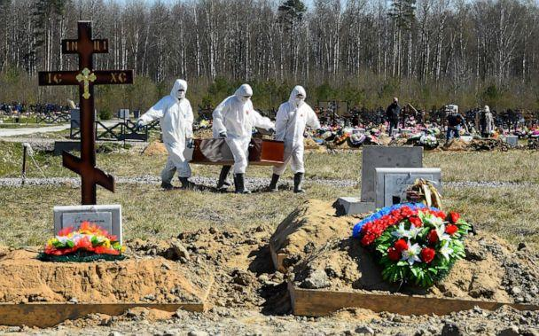 PHOTO: Cemetery workers wearing protective gear bury a COVID-19 victim at a cemetery on the outskirts of Saint Petersburg, Russia, on May 6, 2020. (Olga Maltseva/AFP via Getty Images)