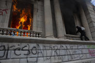 Flames shoot out from a corridor of the Congress building after protesters set a part of the building on fire, in Guatemala City, Saturday, Nov. 21, 2020. Hundreds of protesters were protesting in various parts of the country Saturday against Guatemalan President Alejandro Giammattei and members of Congress for the approval of the 2021 budget that reduced funds for education, health and the fight for human rights. (AP Photo/Oliver De Ros)