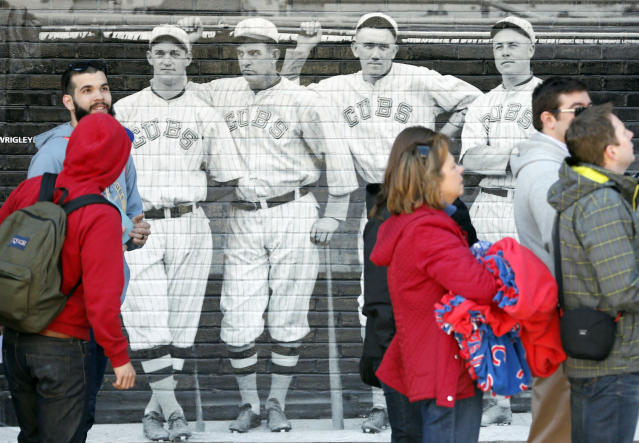 Baseball fans walk past a mural of four 1918 Chicago Cubs' players as they enter Wrigley Field on the 100th anniversary of the first baseball game at the park, before a game between the Arizona Diamondbacks and Chicago Cubs, Wednesday, April 23, 2014, in Chicago. (AP Photo/Charles Rex Arbogast)