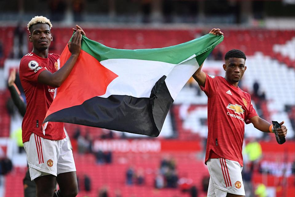 <p>Pogba and Amad display the Palestinian flag</p> (POOL/AFP via Getty Images)
