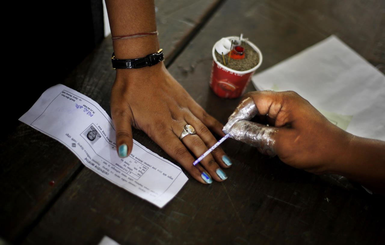 An Indian election officer applies an indelible ink mark on the finger of a woman during the first phase of elections in Dibrugarh, in the northeastern state of Assam, India, Monday, April 7, 2014. India started the world's largest election Monday, with voters in the remote northeast making their way past lush rice paddies and over rickety bamboo bridges to reach the polls. The country's 814 million electorate will vote in stages over the next five weeks. (AP Photo/Altaf Qadri)