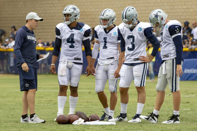 FILE - In this Saturday, July 28, 2018, file photo, Dallas Cowboys quarterback coach Kellen Moore, left talks to quarterbacks Dak Prescott (4), Dalton Sturm (1), Mike White (3) and Cooper Rush, far right, during NFL football training camp in Oxnard, Calif. In one year, Moore has gone from sitting next to Dak Prescott in meetings to running them as the new quarterbacks coach of the Cowboys. (AP Photo/Gus Ruelas, File)