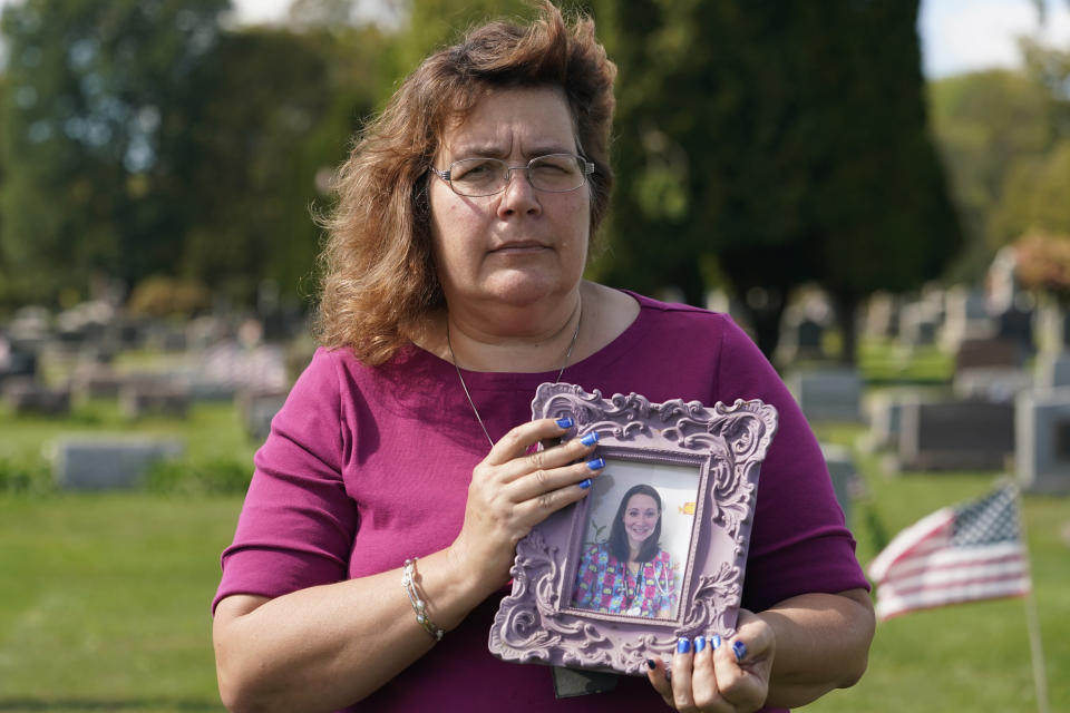 Sharon Grover holds a photograph of her daughter, Rachael, at Fairview Cemetery, Tuesday, Sept. 28, 2021, in Mesopotamia, Ohio. Grover believes her daughter started using prescription painkillers around 2013 but missed any signs of her addiction as her daughter, the oldest of five children, remained distanced. (AP Photo/Tony Dejak)
