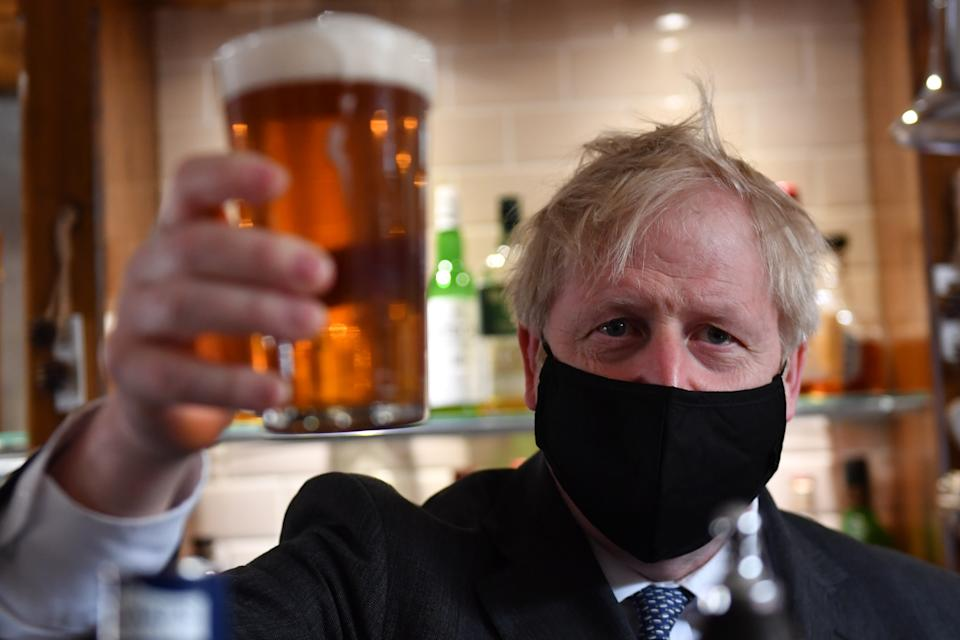 Prime Minister Boris Johnson holds up a pint during a visit to The Mount Tavern public house and restaurant in Wolverhampton, West Midlands, on the local election campaign trail. Picture date: Monday April 19, 2021.