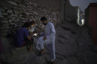 Afghans play games on a cellphone outside their home in Kabul, Afghanistan, Saturday, Sept. 11, 2021. (AP Photo/Felipe Dana)
