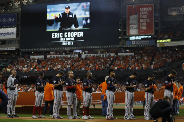 Members of the Washington Nationals stand on the field Tuesday, Oct. 22, 2019, during tribute to umpire Eric Cooper, who died last weekend, before Game 1 of the baseball World Series against the Houston Astros in Houston. (AP Photo/Matt Slocum)