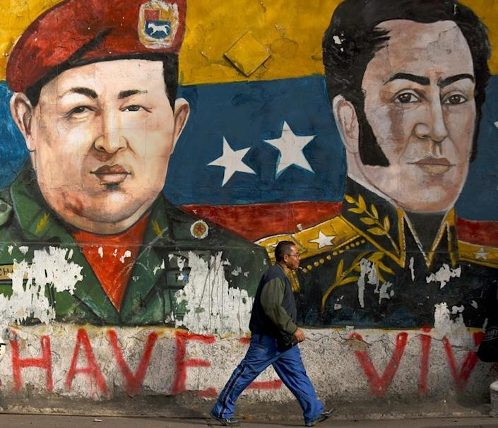 A mural of late Venezuelan president Hugo Chavez (left) and XIX century hero Simon Bolivar on a wall in the low-income Petare neighborhood (AFP Photo/)