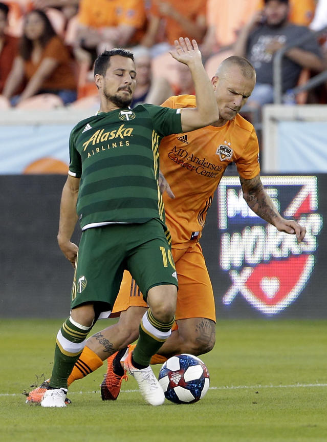 Portland Timbers midfielder Sebastian Blanco (10) falls back as Houston Dynamo defender Aljaz Struna attempts to steal the ball during the first half of an MLS soccer match Wednesday, May 15, 2019, in Houston. (AP Photo/Michael Wyke)