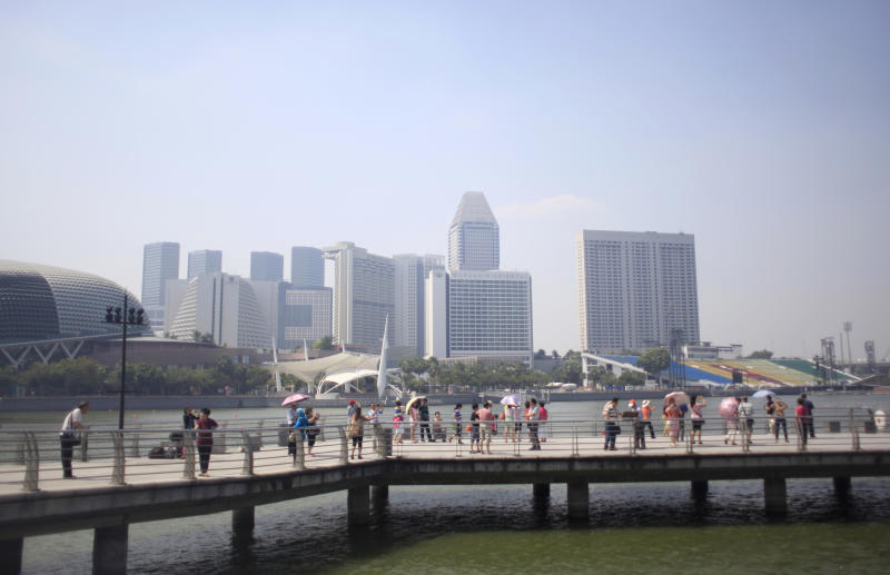 """Tourists visit a look-out point while the Singapore city skyline is seen partially covered in haze in the background, Tuesday, June 18, 2013 in Singapore. The Pollutant Standards Index, Singapore's main measure to determine air quality, crept into the """"unhealthy"""" classification Monday as smoke from roaring blazes on Indonesia's Sumatra island drifted across the sea and cast a gray pall over the city-state's skyscrapers. (AP Photo/Wong Maye-E)"""