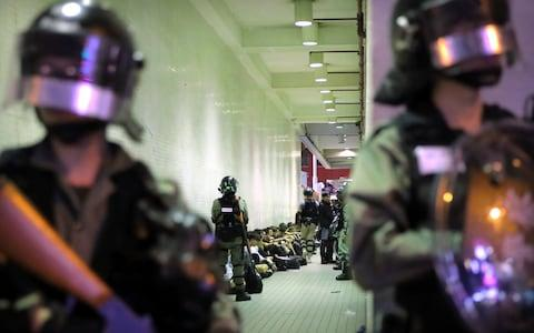 Police in riot gear stand over people detained during a protest in Hong Kong earlier this month - Credit: AP Photo/Kin Cheung, File
