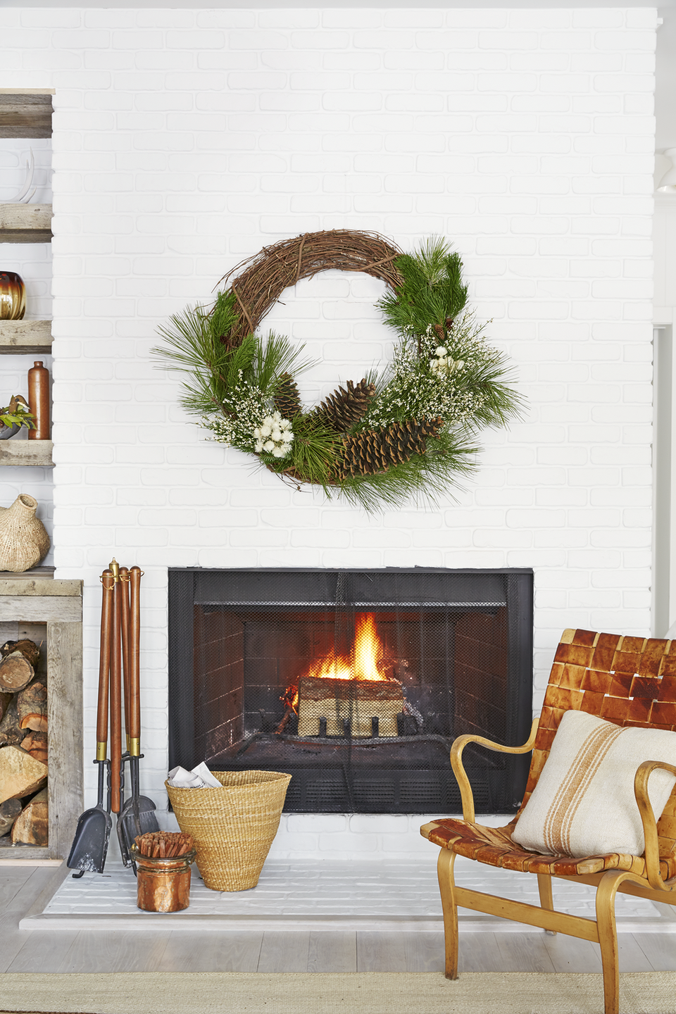 <p>Trade garland and twinkle lights for this gorgeous wreath, embellished with large pinecones, fresh greens, and winter white flowers. </p>
