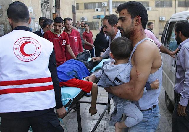 A Syrian man carries a child as they await treatment at a hospital in the regime-held part of Aleppo, on October 13, 2016 (AFP Photo/George Ourfalian)