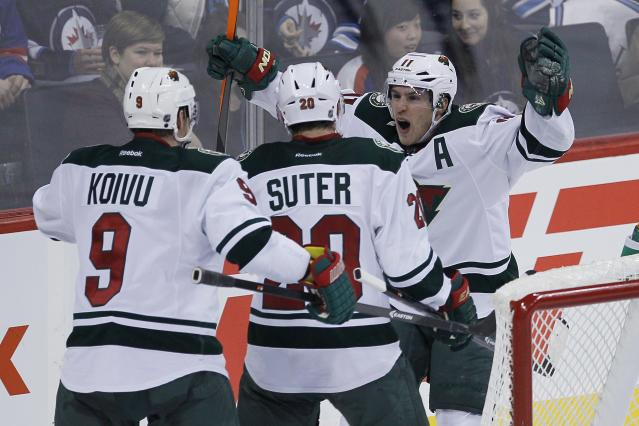 Minnesota Wild's Zach Parise, right, celebrates his goal with teammates Mikko Koivu (9) and Ryan Suter (20) during the third period of an NHL game against the Winnipeg Jets in Winnipeg, Manitoba, Saturday, Nov. 23, 2013. (AP Photo/The Canadian Press, John Woods)