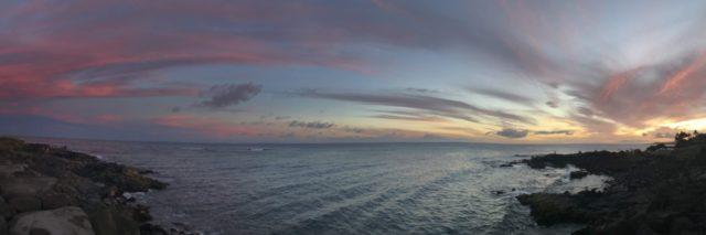panoramic photo of a sunset over the ocean, taken from the top of a cliff