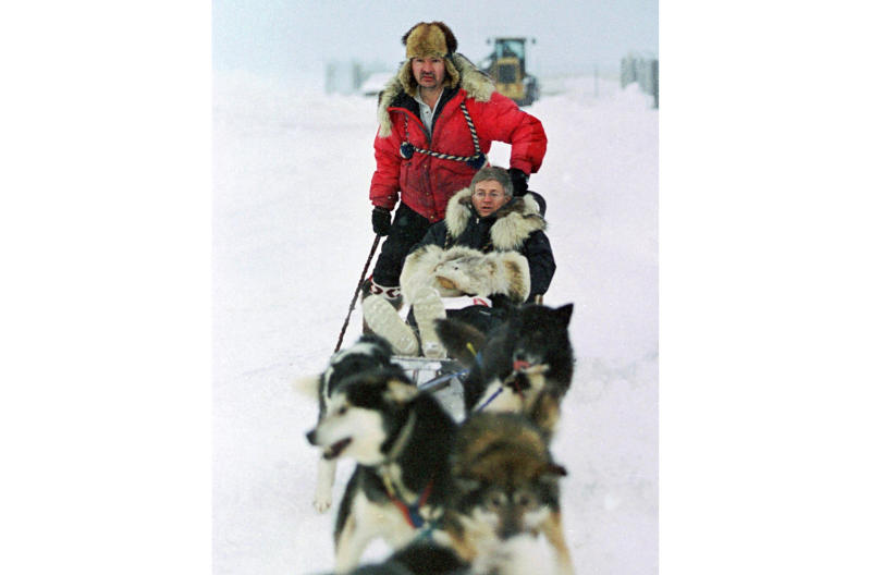 FILE - In this Jan. 19, 2000 file photo, U.S. Census Bureau director Kenneth Prewitt, seated, gets a dog sled ride into town by Harold Johnson after arriving for the first count in the Eskimo village of Unalakleet, Alaska. The 2020 Census kicks off Tuesday, Jan. 21, 2020, in a remote town of Alaska. To mark the occasion, The Associated Press is republishing an article from 20 years ago, when the census began in the village of Unalakleet. (AP Photo/Al Grillo, File)