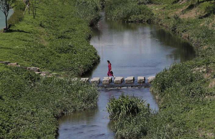 A woman wearing a face mask to help protect against the spread of the new coronavirus crosses a stream in Seoul, South Korea, Wednesday, July 15, 2020. (AP Photo/Lee Jin-man)
