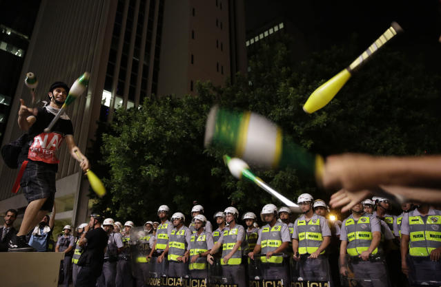 "Demostrators surrounded by riot police juggle pins as they protest against money spent on the World Cup preparations in Sao Paulo, Brazil, Thursday, March 13, 2014. Thursday, Brazilian Sports Minister Aldo Rebelo guaranteed ""the World Cup in Brazil will be the safest"" in history even though widespread demonstrations are expected across the country to protest against corruption, poor public services and the billions of dollars being spent on the World Cup and 2016 Olympics in Rio de Janeiro. (AP Photo/Andre Penner)"