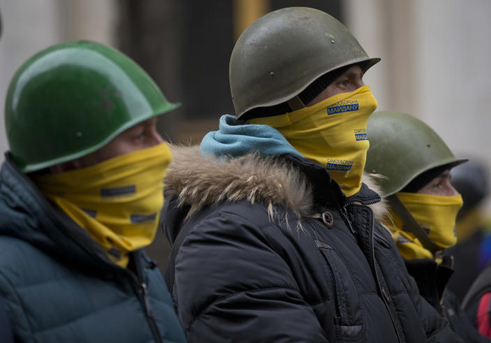 Protesters stand guard in front of presidential administrative building in central Kiev, Ukraine, Saturday, Feb. 22, 2014. Protesters in the Ukrainian capital claimed full control of the city Saturday following the signing of a Western-brokered peace deal aimed at ending the nation's three-month political crisis. The nation's embattled president, Viktor Yanukovych, reportedly had fled the capital for his support base in Ukraine's Russia-leaning east. (AP Photo/Darko Bandic)