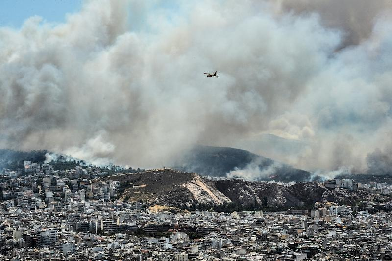 A firefighters' helicopter flies over as smoke billows over the outskirts of Athens on July 17, 2015 as firemen battled a brush fires in the northeast of the city and in the southern Pelopponese peninsula that prompted the evacuation of five villages (AFP Photo/Andreas Solaro)