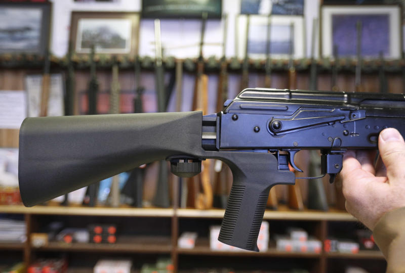 A bump stock device, which fits on a semi-automatic rifle to increase the firing speed, is installed on an AK-47 at a gun store.