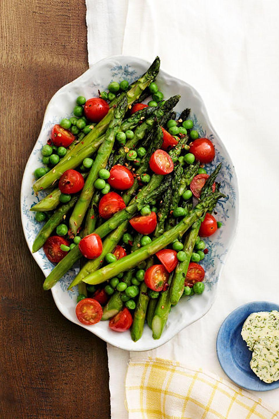 "These garden-fresh vegetables are full of flavor. Sauteed lightly in olive oil and garlic then served with homemade herb butter, they're the perfect addition to any meal. <a href=""https://www.countryliving.com/food-drinks/recipes/a4959/asparagus-peas-tomatoes-herb-butter-recipe-clx0414/"" rel=""nofollow noopener"" target=""_blank"" data-ylk=""slk:Get the recipe."" class=""link rapid-noclick-resp""><strong>Get the recipe.</strong></a>"