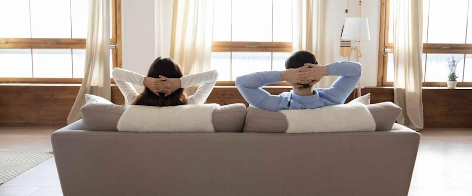 Full length rear view of young couple relaxing on sofa in modern home  don't refinance their mortgage.